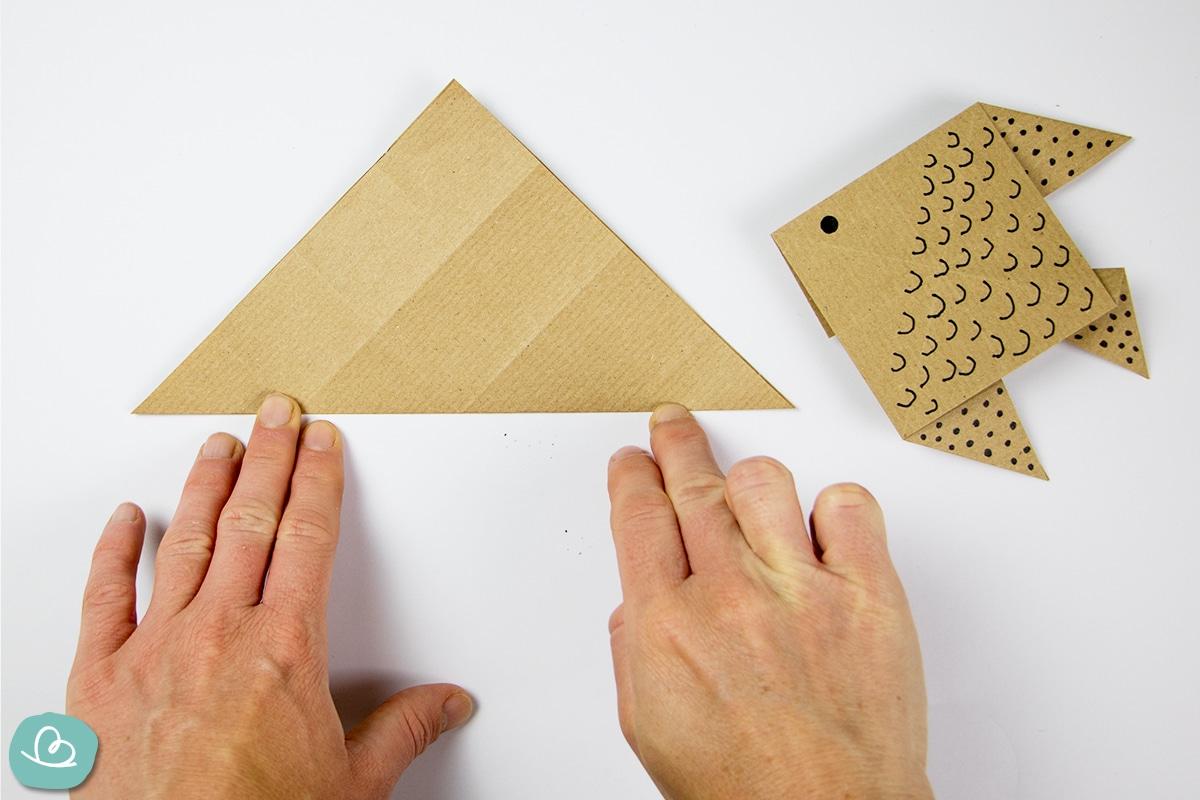 Mit den Händen falten und Fisch aus Papier