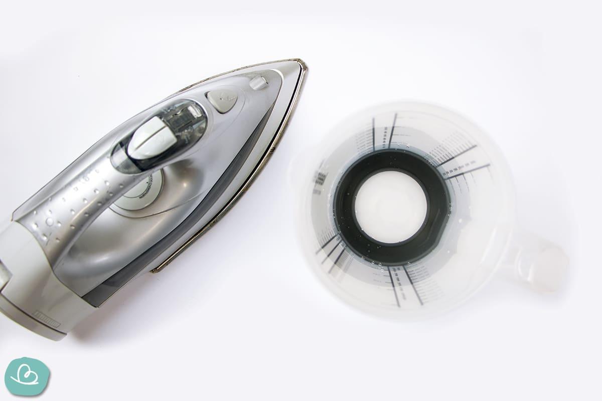 Bügeleisen und Messbecher mit Wasser