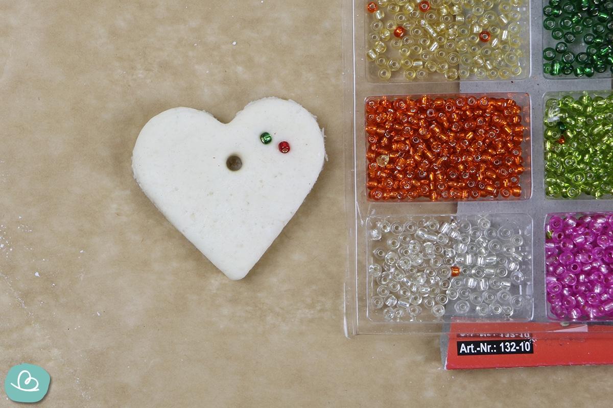 Perlen in Salzteig drücken