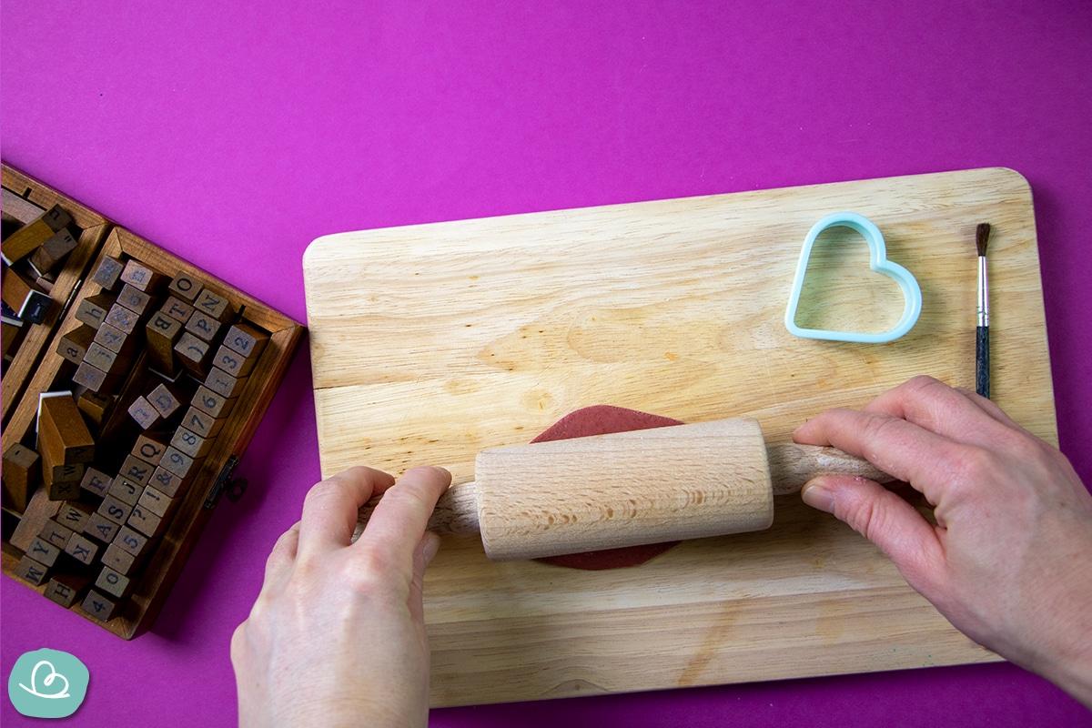 Rote Modelliermasse auf einem Holzbrett ausrollen.