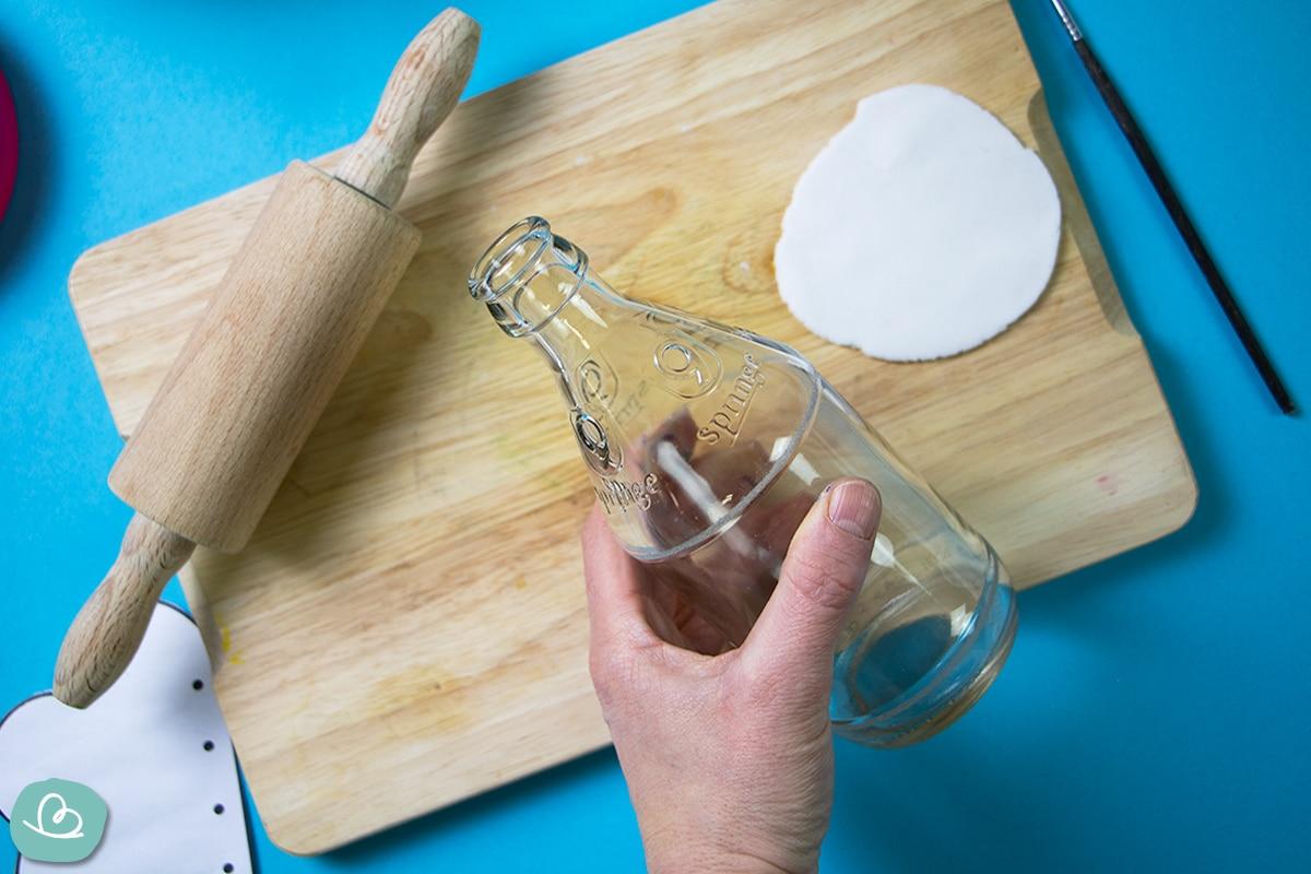 Nudelholt, leere Glasflasche und ausgerollte Modelliermasse auf einem Holzbrett.