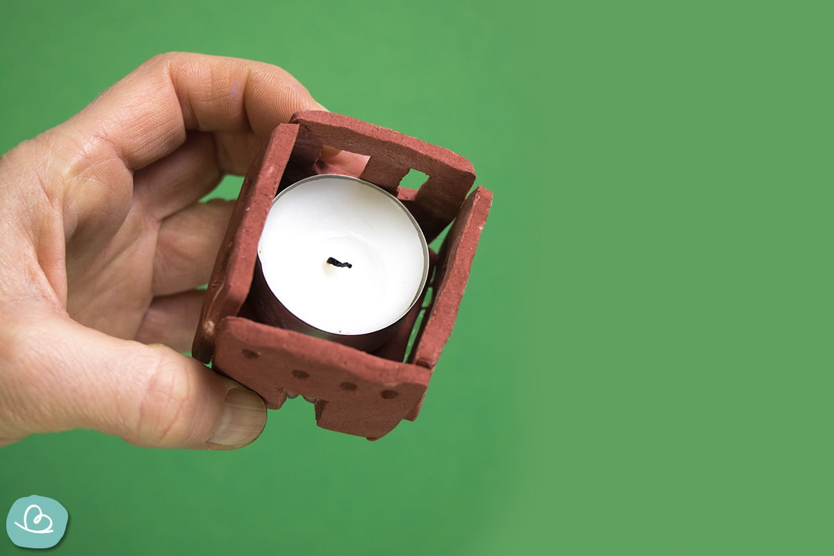 Viereckiger, roter Teelichthalter mit Teelicht in der Hand haltend.