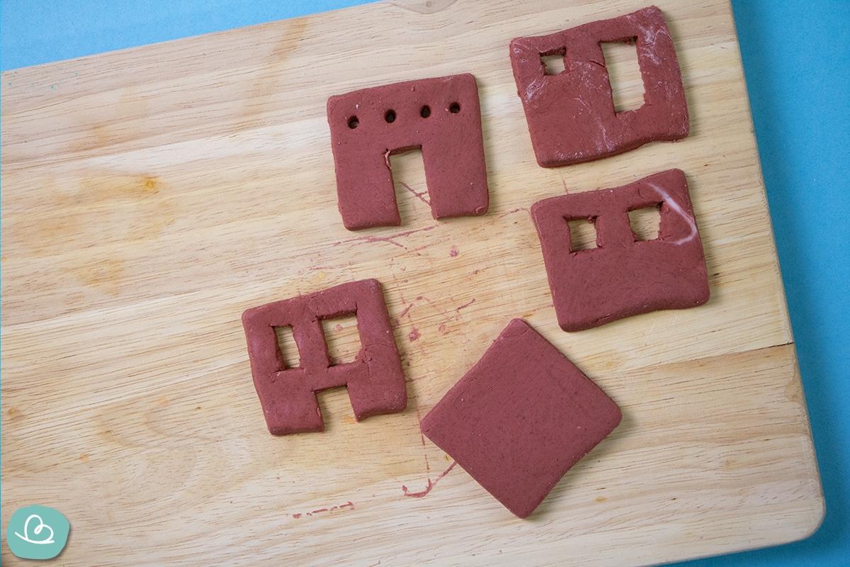 Fünf rote Vierecke aus Modelliermasse auf einem Holzbrett.