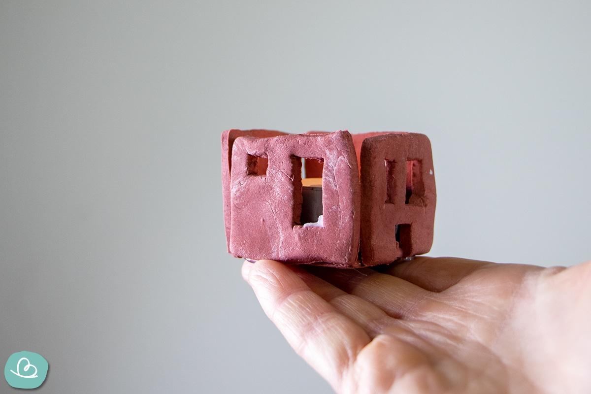Kleines rotes Haus ohne Dach aus Modelliermasse.