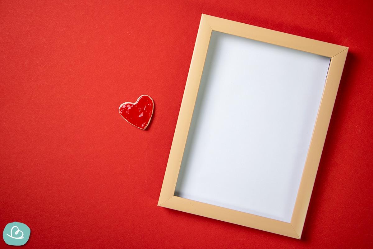 Rotes Herz neben einem Bilderrahmen auf roten Tonpapier.