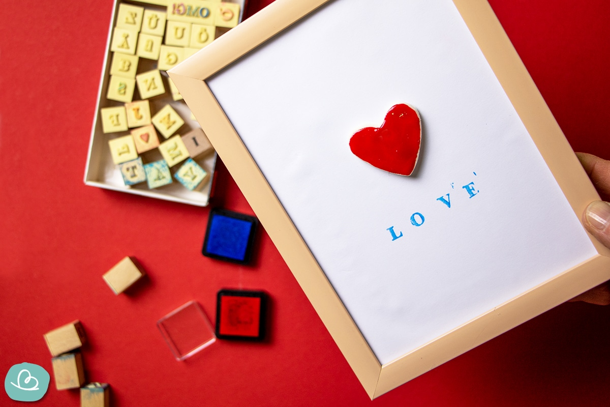 Bilderrahmen mit roten Herz. Darunter steht in Druckbuchstaben Love.