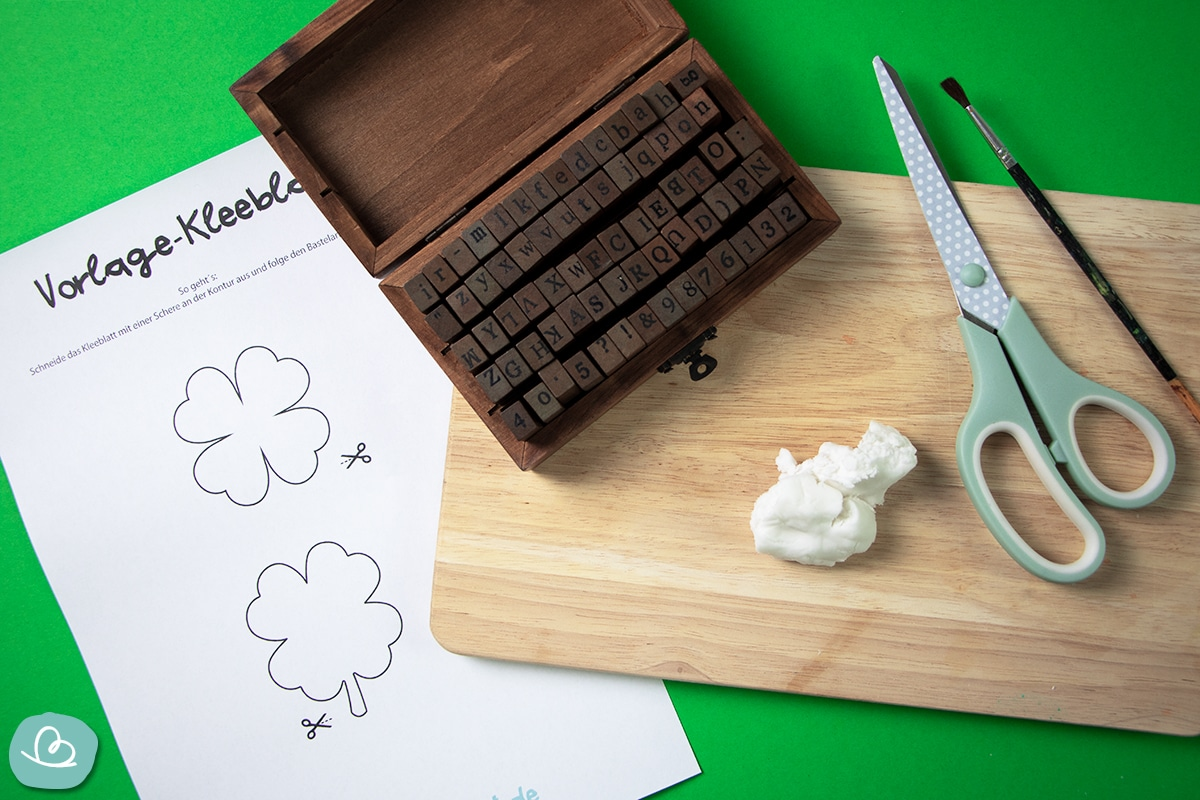 Modelliermasse, Schere, Pinsel, Stempel, Bastelvorlage auf einem Holzbrett.