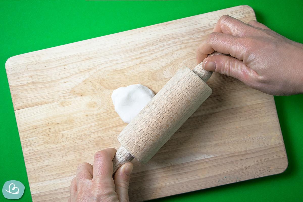 Modelliermasse wird mit einem Nudelholz ausgerollt.
