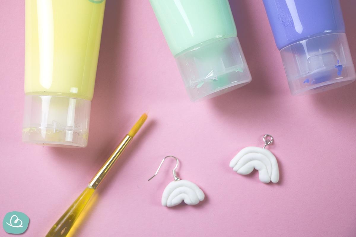 Acrylfarbe, Pinsel und Ohrringe.