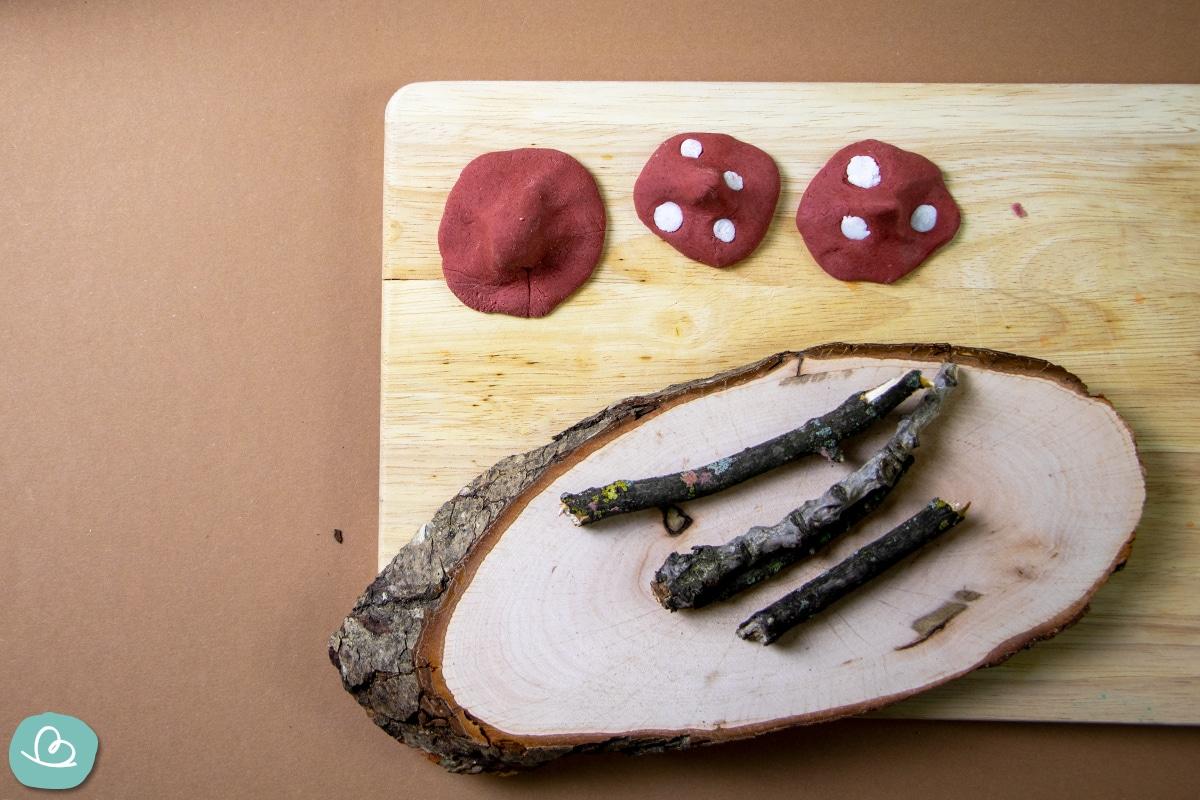 Holzbrett mit Modelliermasse und Ästen.