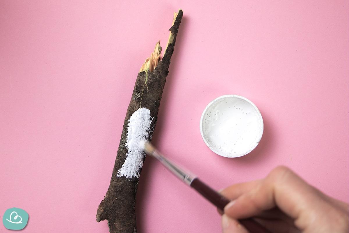 Ast mit weißer Farbe anmalen.