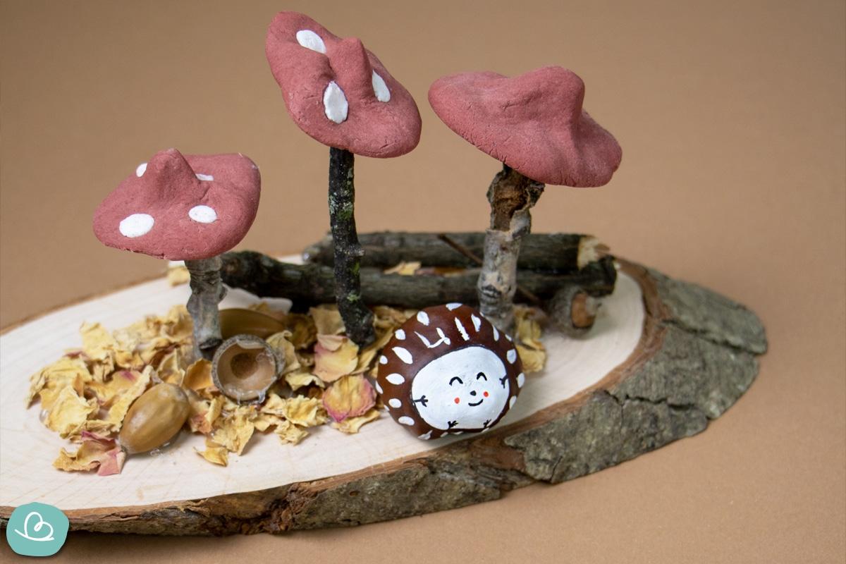Kleine Zweige, Pilze und bemalte Kastanien auf Holzplatte. Stillleben aus Naturmaterialien.