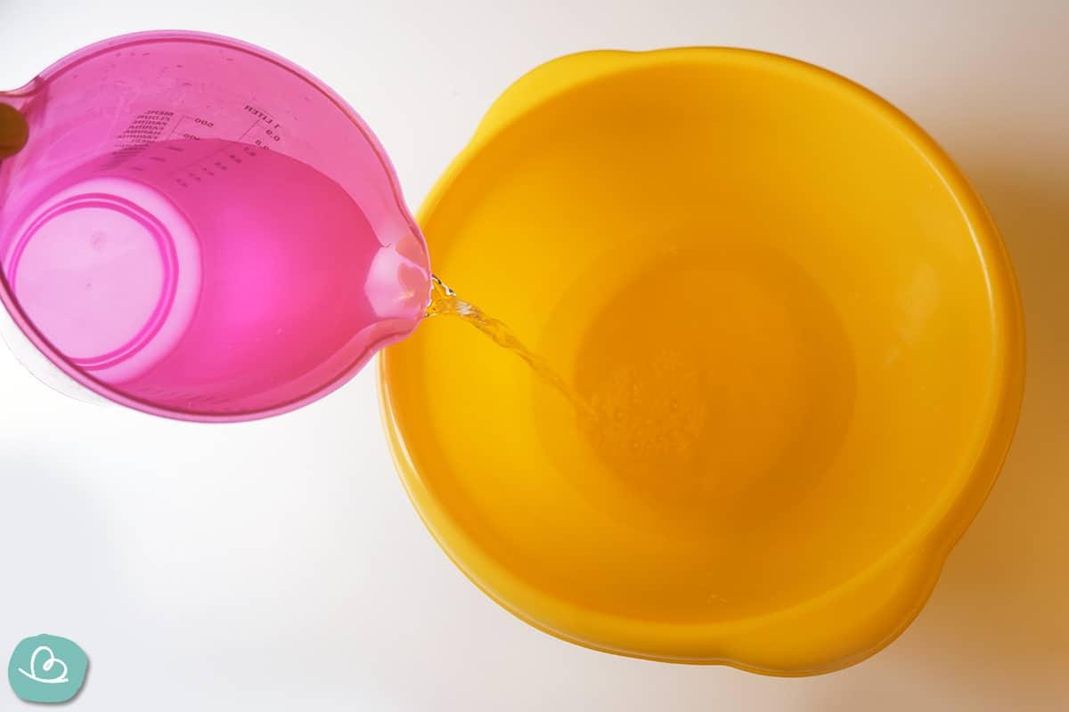 Wasser in eine gelbe Schüssel gießen.