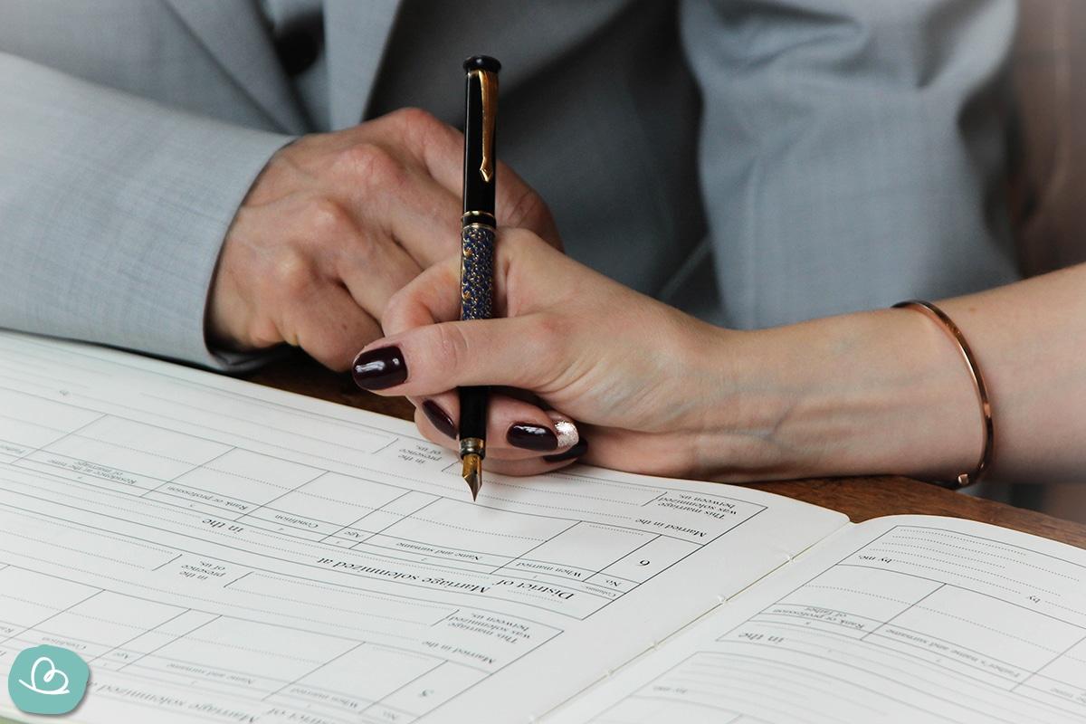 Ein Mann und eine Frau unterschreiben im Grundbuch.