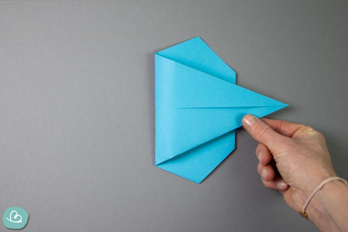 Papierspitze mit dem Daume und Zeigefinger nach rechts falten.