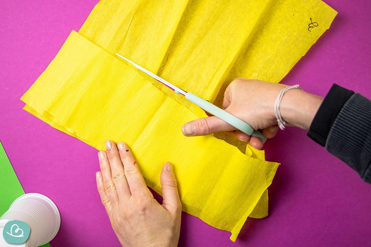 Streifen aus gelben Krepppaiper schneiden.