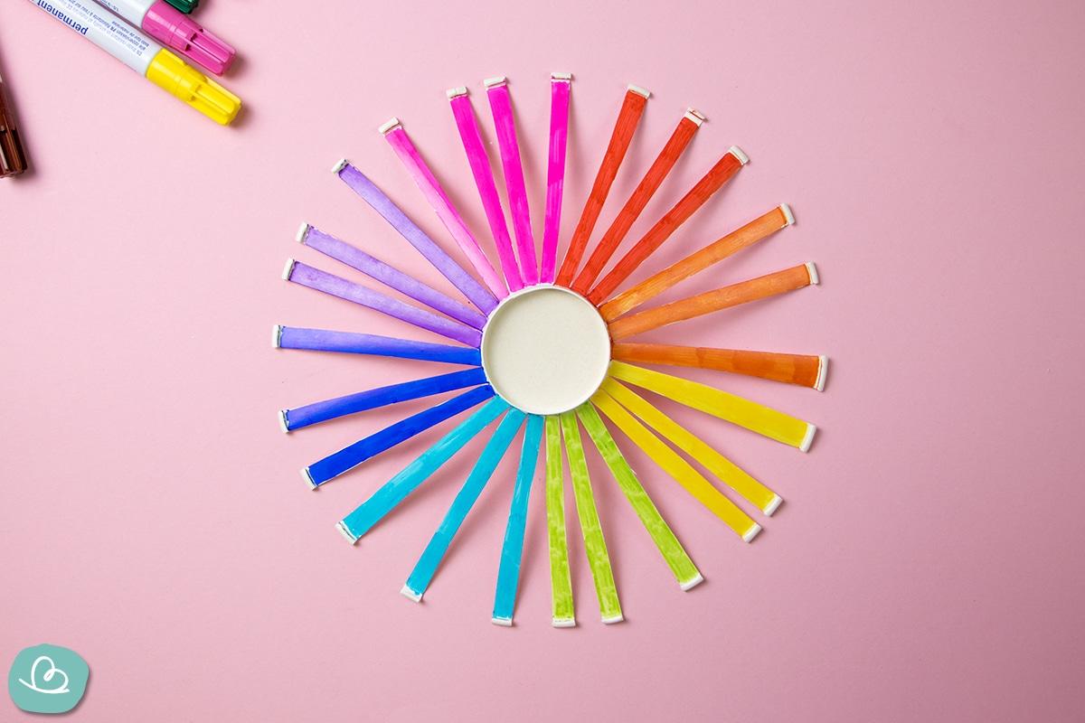 Eingeschnittener Pappbecher in Regenbogenfarben.
