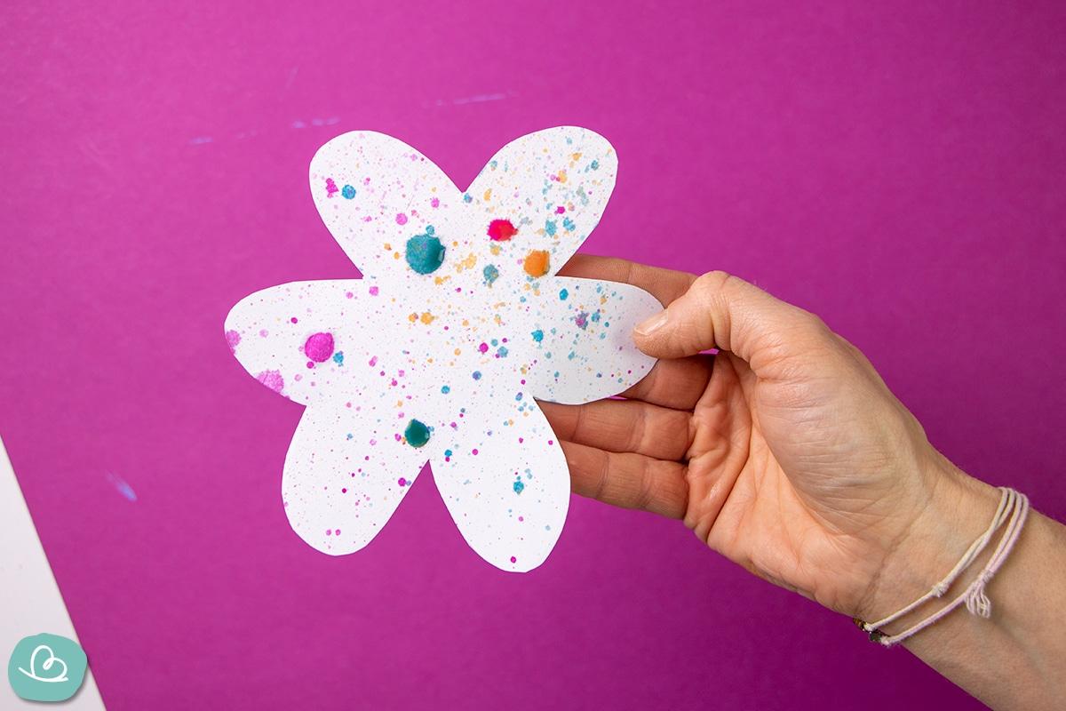 Bunte Spritzer aus Wasserfarbe auf einer Papierblume.