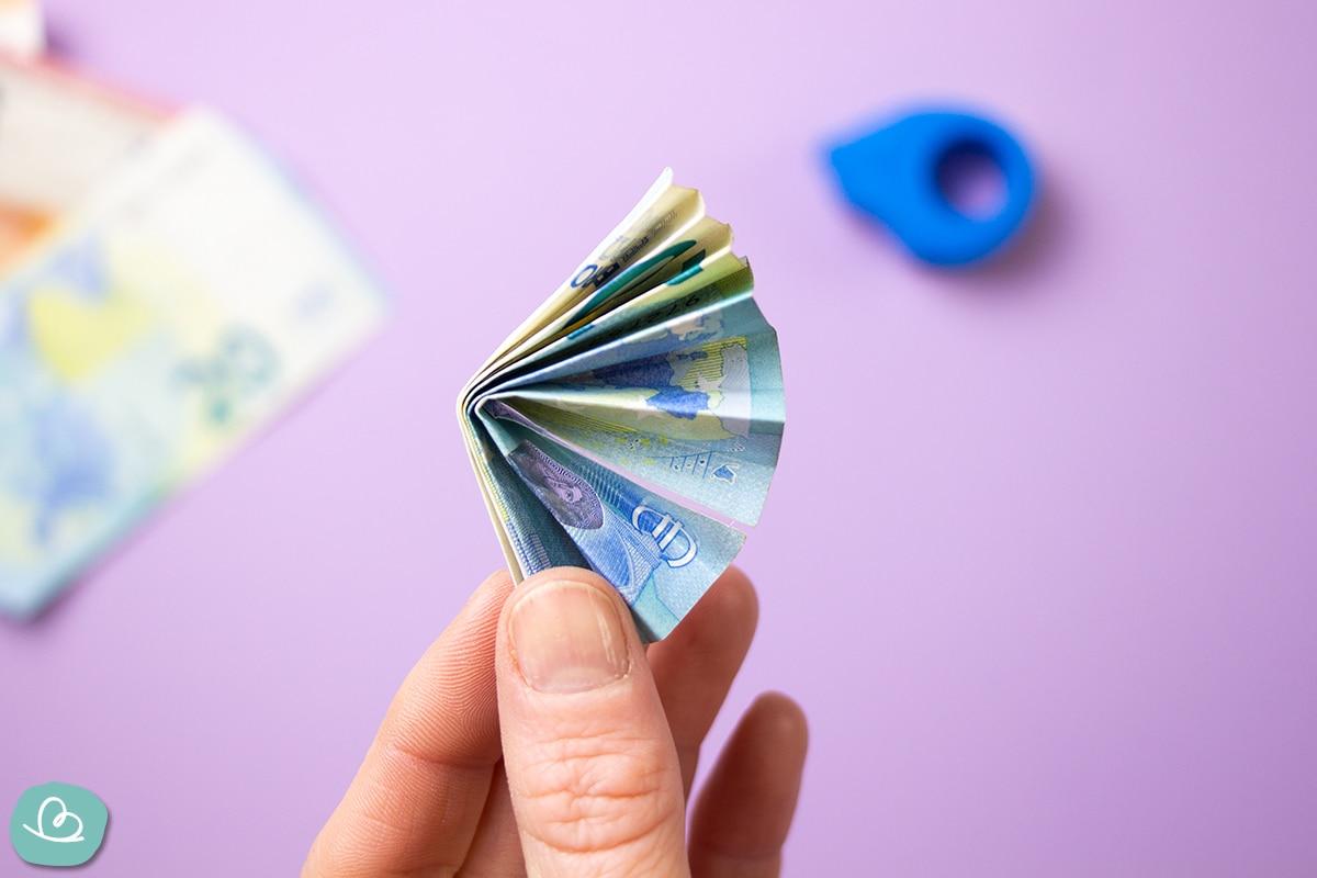 Eine Hand hält einen gefalteten Geldschein