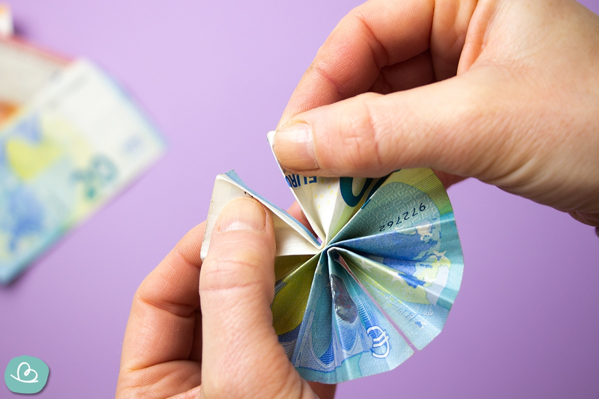 Zwei Hände halten einen gefalteten Geldschein.