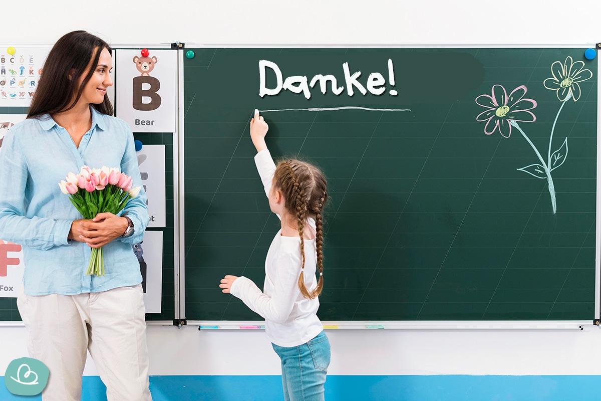 Kind schreibt Danke an eine grüne Tafel.