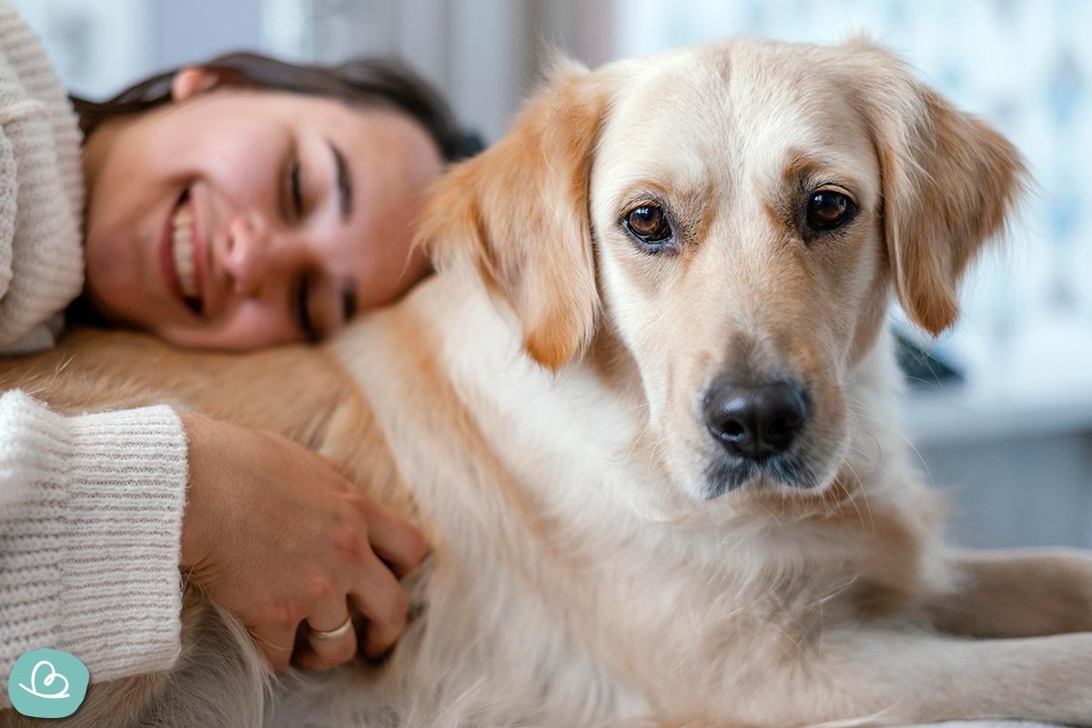 Eine junge Frau kuschelt mit einem Hund.