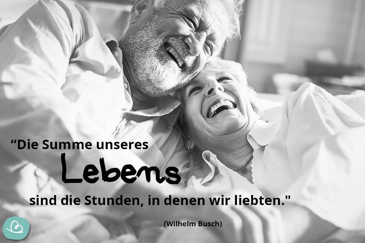 Älteres Ehepaar sitzen lachend nebeneinander auf einem Sofa.