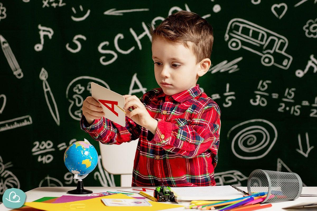 Ein Schulanfänger liest eine Glückwunschkarte.