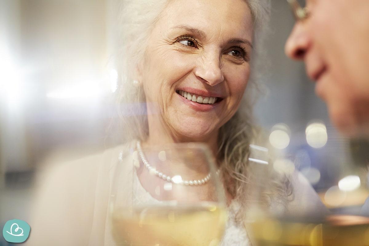 Ältere mit weißen Haaren und Perlenkette stößt mit einem Weinglas an.