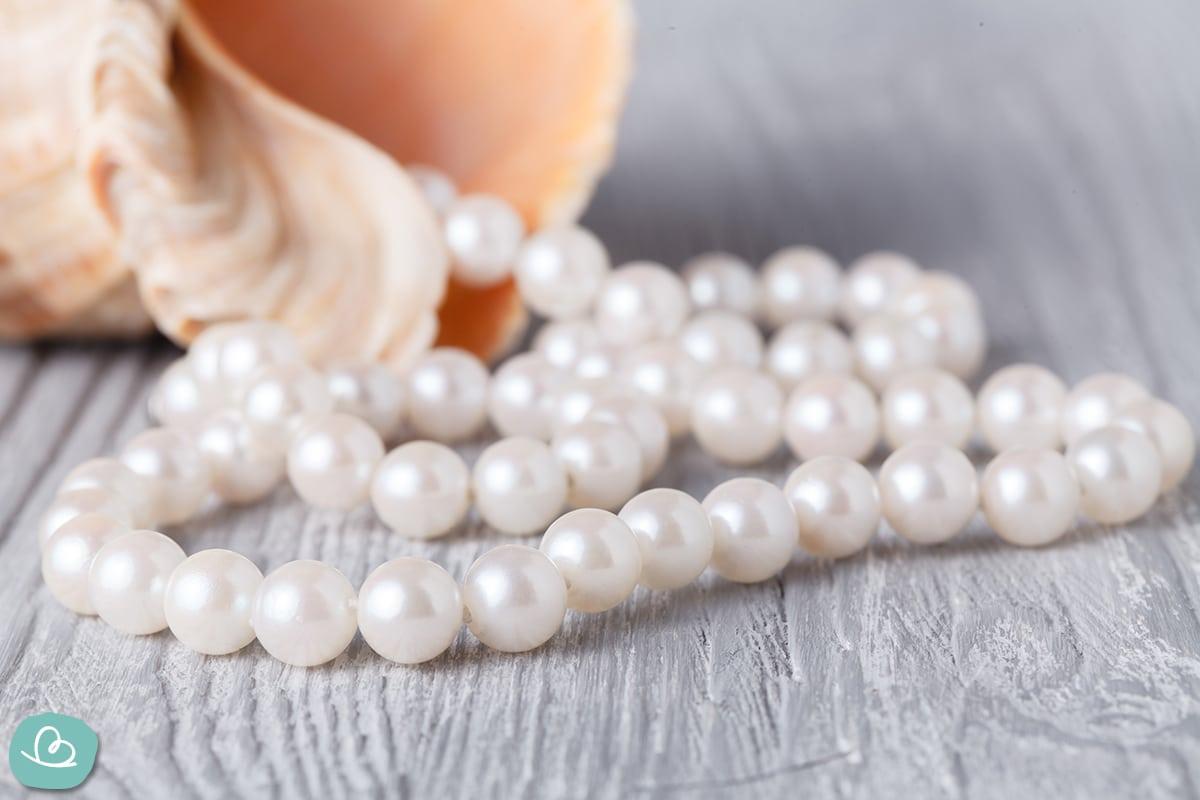 Perlenkette auf einem grauen Holztisch.