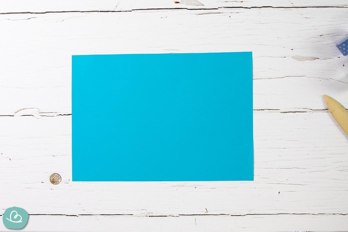 Blaues A4 Tonpapier auf einem Holztisch.