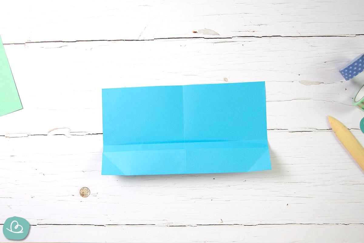 Blaues Papier zu einem Umschlag falten.