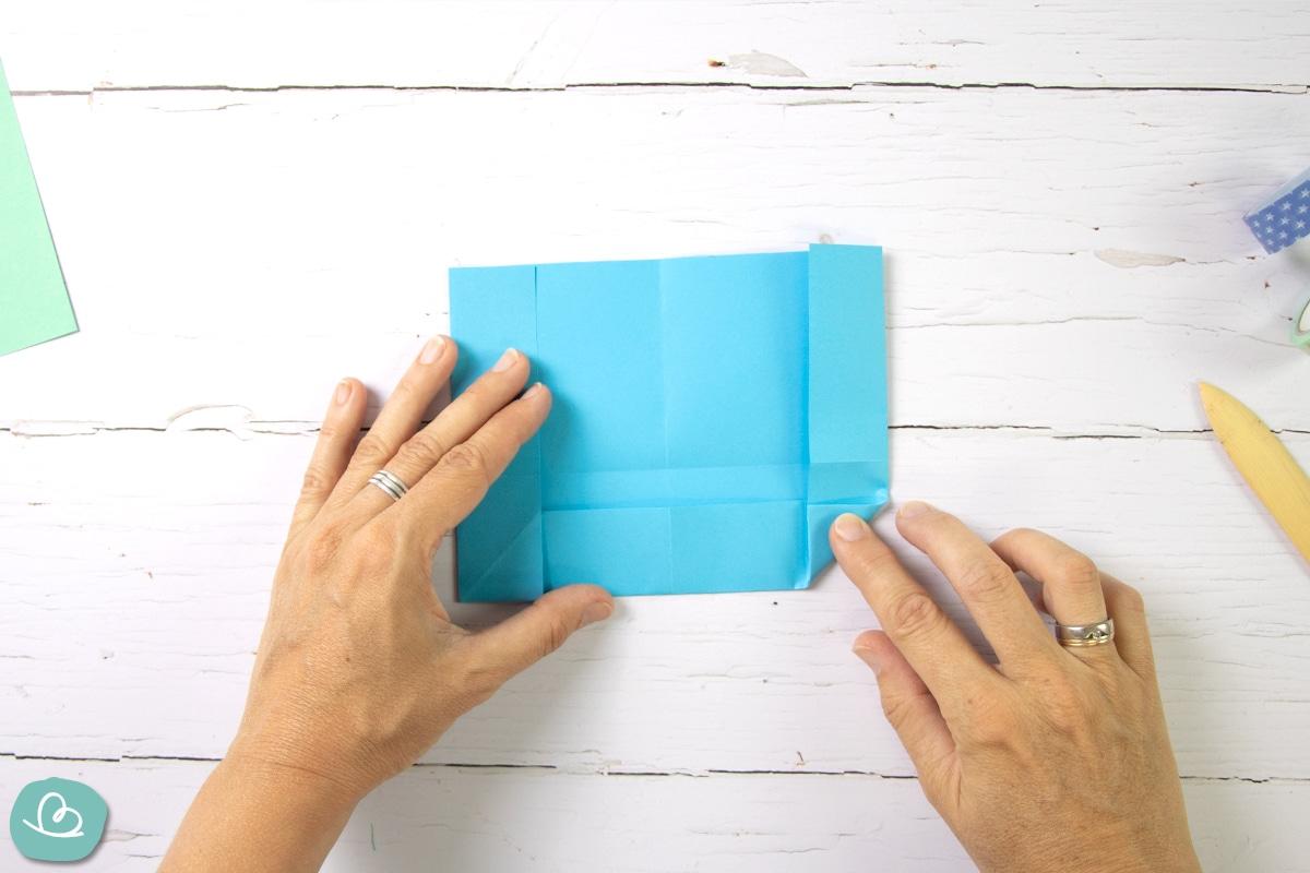 Papierecke mit der Hand falten.
