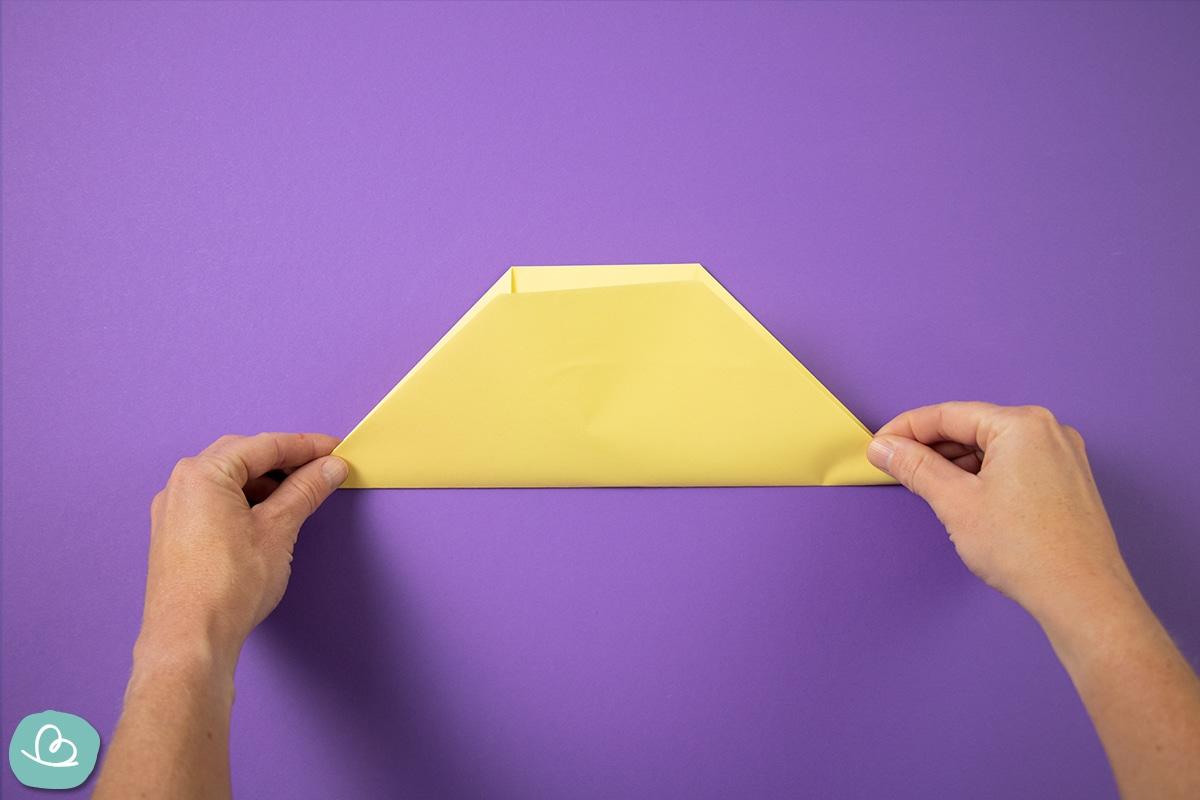 Papier mit beiden Händen nach oben falten.
