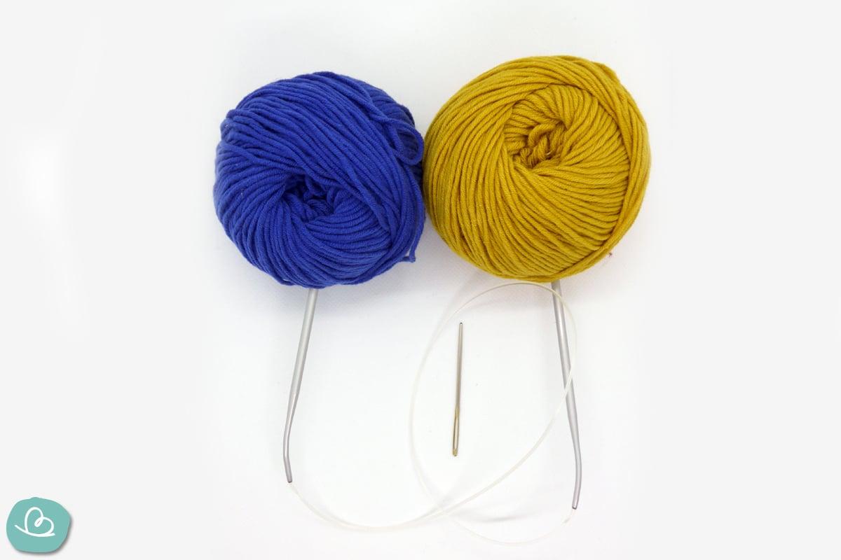 blau und gelbe Wolle mit Stricknadeln