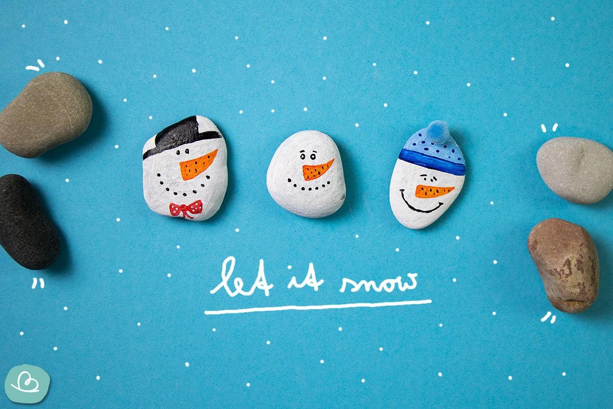 Bemalte Steine als Schneemänner.